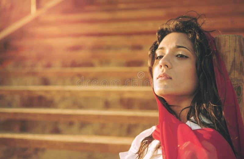 La ragazza Mediterranea che si siede sulle scale riscalda l'effetto applicato fotografia stock