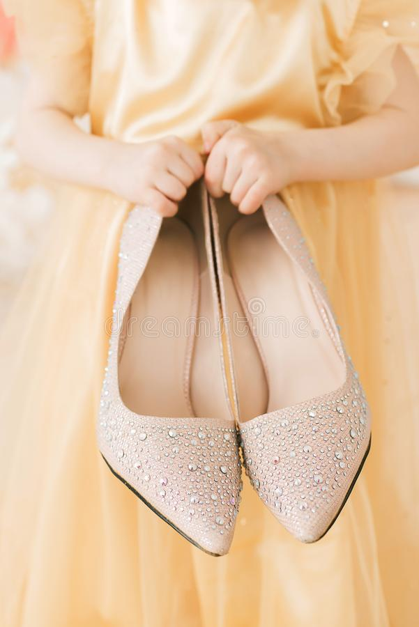 La ragazza mette sopra le scarpe di sua madre Le scarpe della madre in mani dei bambini immagini stock libere da diritti