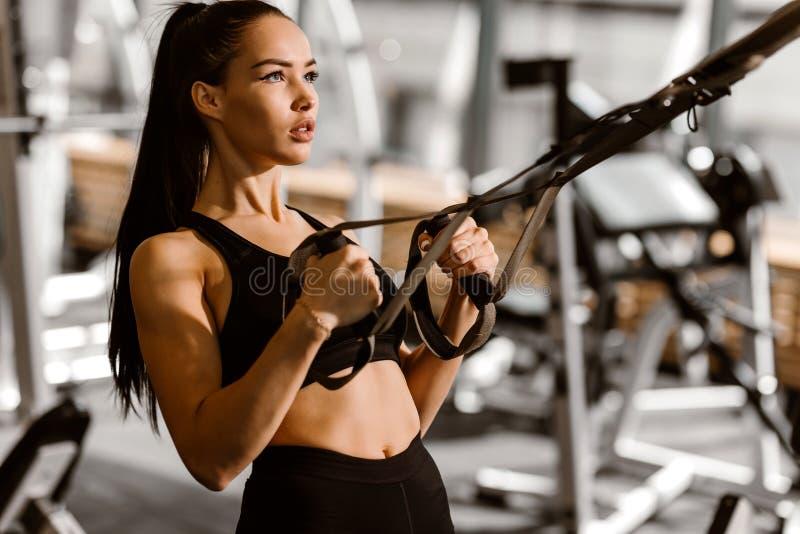 La ragazza mora atletica vestita negli sport neri superiori e mette sta risolvendo sulla forma-stazione nella palestra immagini stock