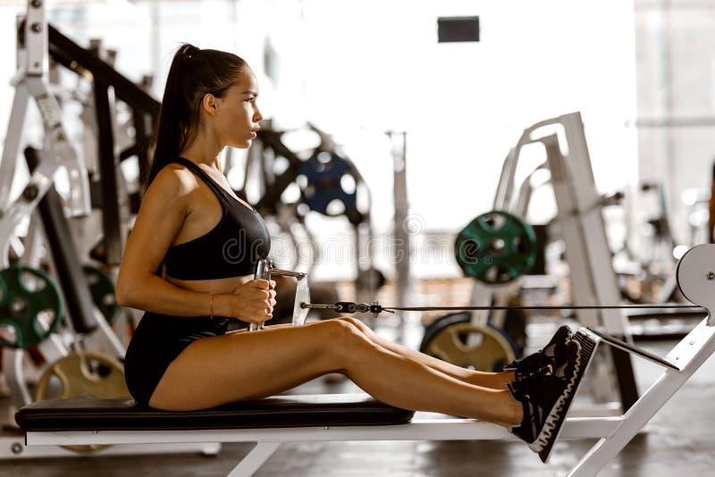 La ragazza mora atletica vestita negli sport neri superiori e mette sta risolvendo sulla macchina di esercizio nella palestra immagine stock
