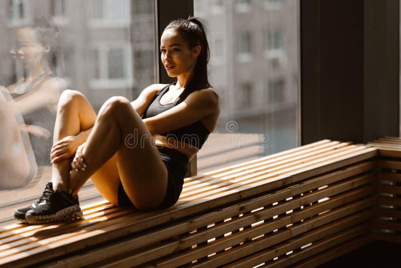 La ragazza mora atletica vestita negli sport neri superiori e mette sta sedendosi su un davanzale di legno della finestra nella p fotografia stock libera da diritti