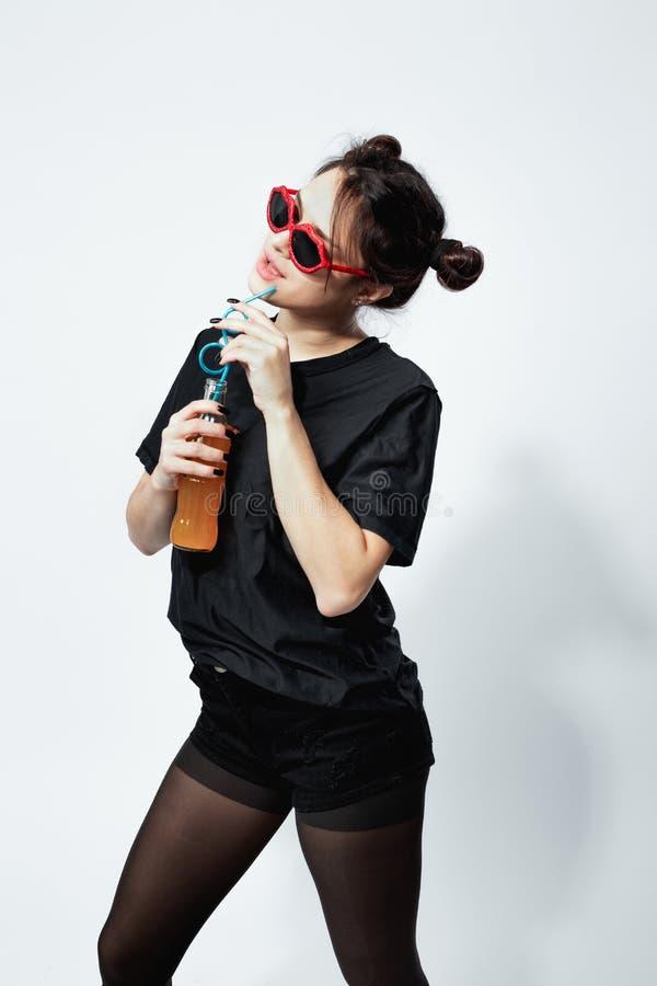 La ragazza mora divertente in una cima nera, mette, calzamaglia, cappuccio e gli occhiali da sole rossi sta bevendo il succo dall fotografia stock