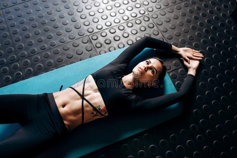 La ragazza mora esile con il tatuaggio vestito in vestiti neri di sport sta trovandosi sulla stuoia per forma fisica nella palest fotografia stock libera da diritti