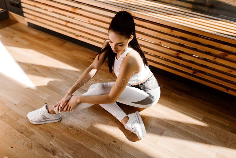 La ragazza mora esile vestita in vestiti bianchi di sport si siede sul pavimento vicino alla finestra nella palestra fotografie stock