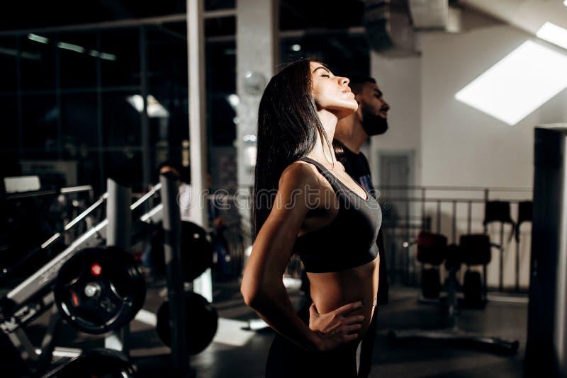 La ragazza mora esile vestita in vestiti neri di sport e la vettura di forma fisica stanno facendo il riscaldamento nella palestr immagine stock