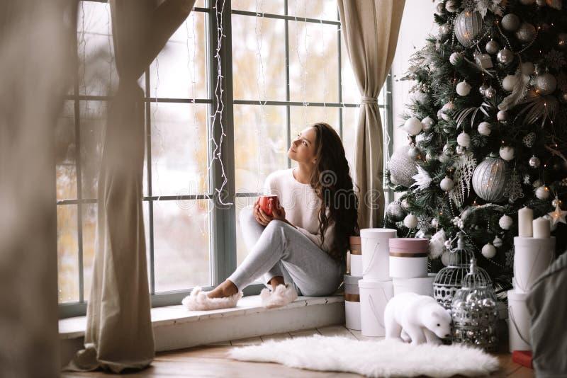 La ragazza mora incantante vestita in pantaloni, maglione e pantofole calde tiene una tazza rossa che si siede sul davanzale dell immagini stock libere da diritti