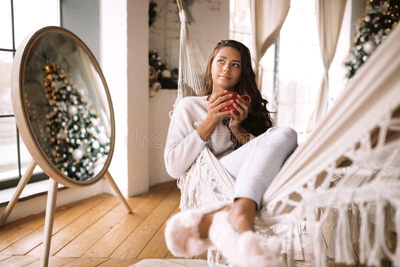 La ragazza mora incantante vestita in pantaloni, maglione e pantofole calde tiene una tazza rossa che si trova in un'amaca in un  immagine stock libera da diritti