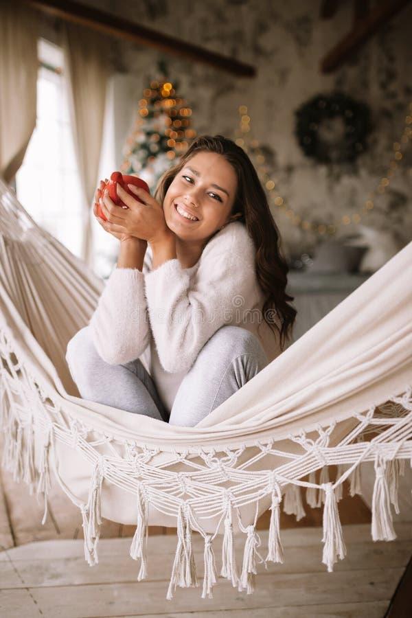 La ragazza mora sorridente vestita in pantaloni, maglione e pantofole calde tiene una tazza rossa che si siede in un'amaca in un  immagini stock libere da diritti