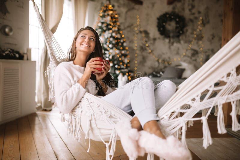 La ragazza mora sorridente vestita in pantaloni, maglione e pantofole calde tiene una tazza rossa che si trova in un'amaca in un  fotografie stock libere da diritti