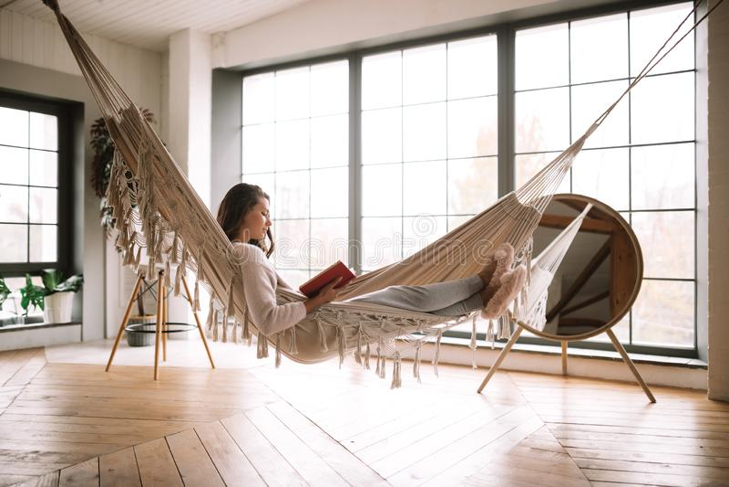 La ragazza mora vestita in pantaloni, maglione e pantofole calde legge un libro che si trova in un'amaca in una stanza accoglient fotografia stock