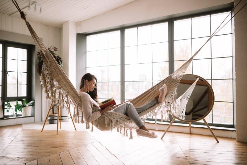 La ragazza mora vestita in pantaloni, maglione e pantofole calde legge un libro che si trova in un'amaca in una stanza accoglient immagini stock libere da diritti