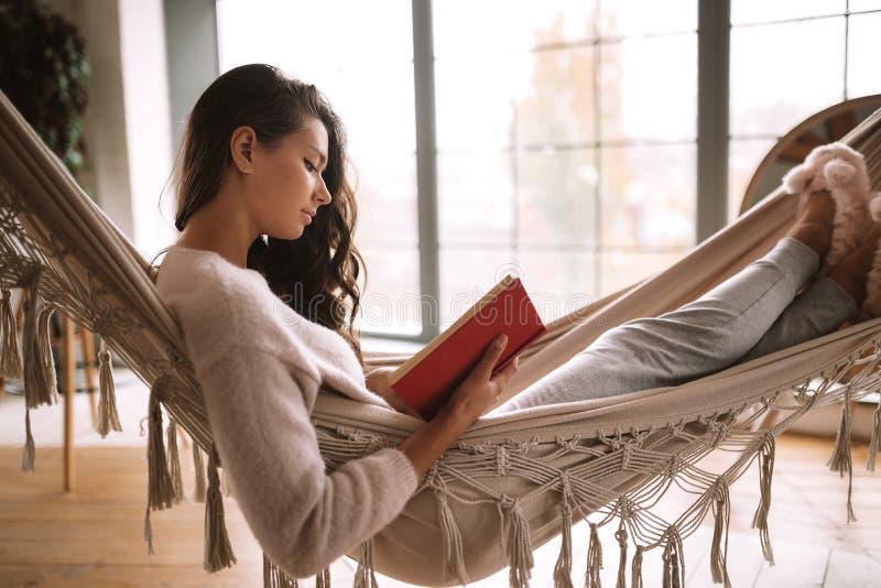 La ragazza mora vestita in pantaloni, maglione e pantofole calde legge un libro che si trova in un'amaca in una stanza accoglient immagine stock