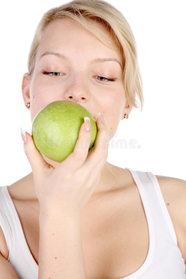 La ragazza morde fuori dalla mela immagini stock libere da diritti