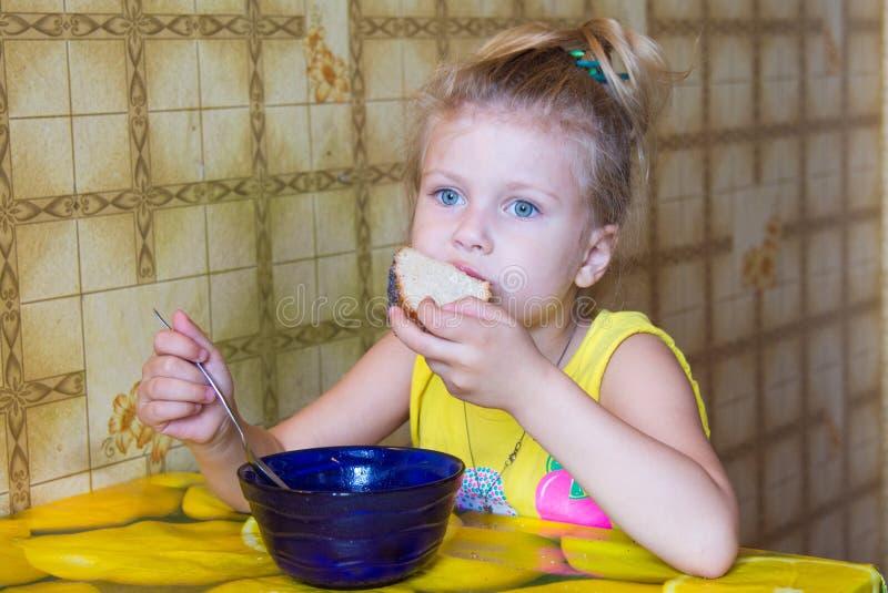la ragazza morde fuori un pezzo di pane che mangia la minestra fotografie stock libere da diritti