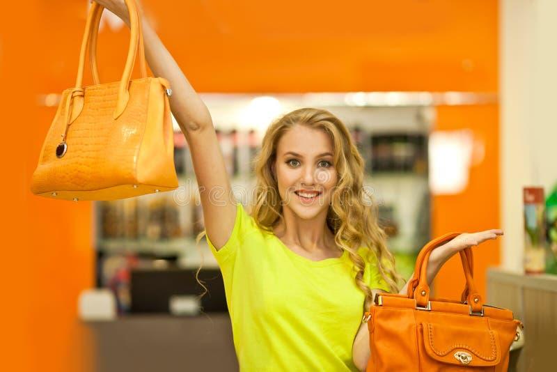 La ragazza mostra due borse di cuoio arancio che esaminano la macchina fotografica immagine stock