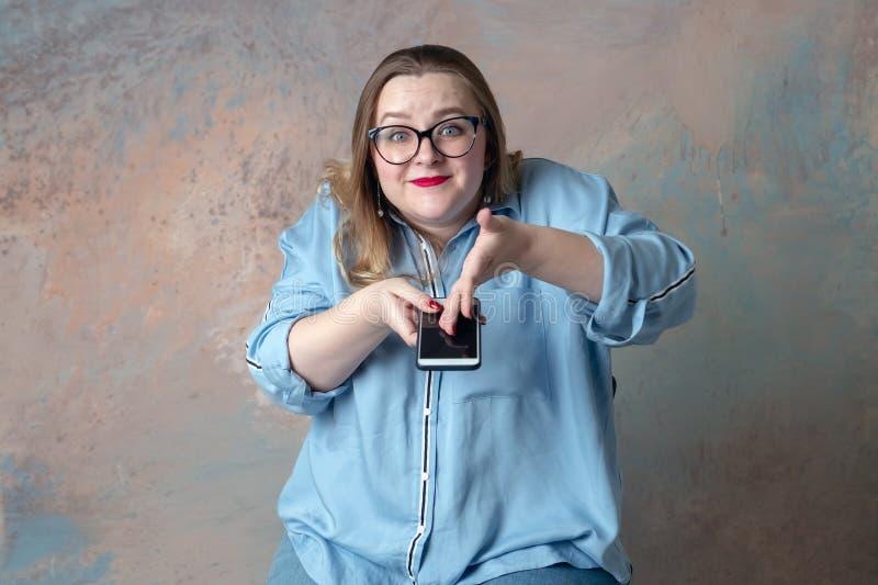 La ragazza mostra emozionalmente sul telefono fotografie stock libere da diritti