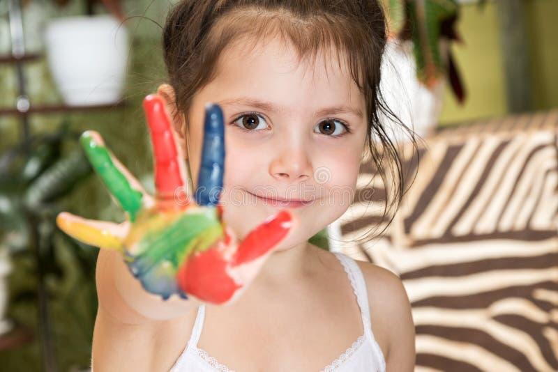 La ragazza mostra la palma spalmata in pittura fotografia stock