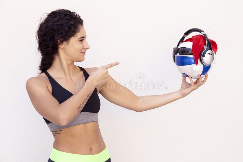 La ragazza mostra un pallone da calcio con i vetri fotografia stock