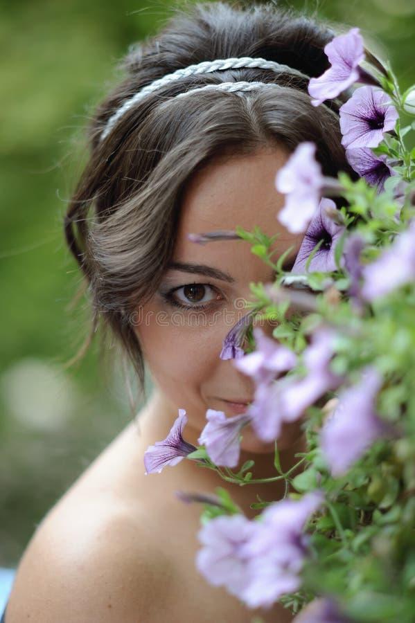 La ragazza nasconde il fronte nei fiori di primavera fotografie stock libere da diritti