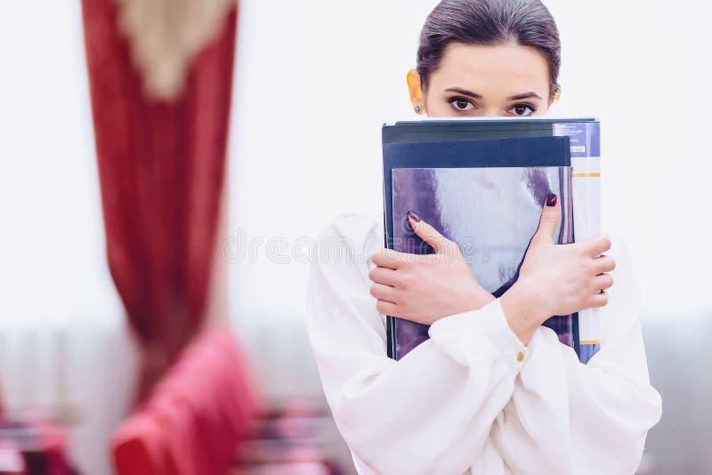 la ragazza nasconde il suo fronte dietro i documenti fotografia stock