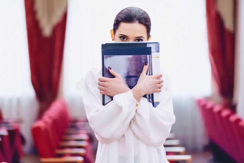 la ragazza nasconde il suo fronte dietro i documenti immagine stock
