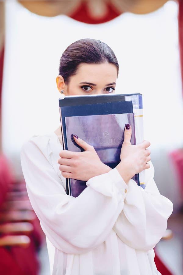 la ragazza nasconde il suo fronte dietro i documenti fotografia stock libera da diritti