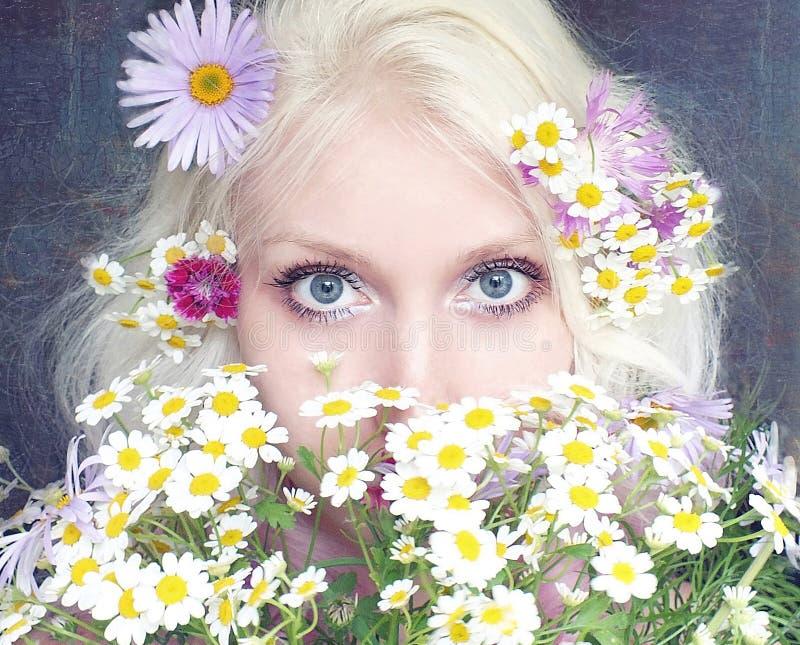 La ragazza nasconde il suo fronte dietro un mazzo delle margherite fotografie stock