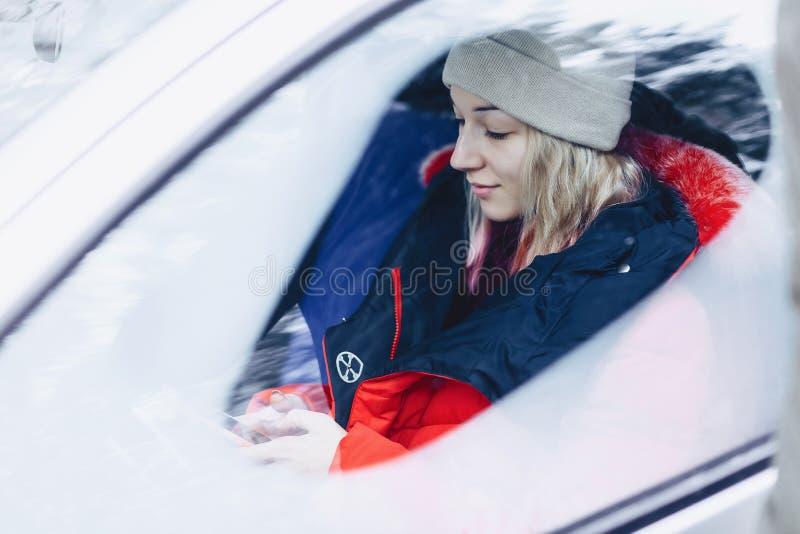 La ragazza nei vestiti dell'inverno nell'automobile esamina il telefono immagini stock libere da diritti