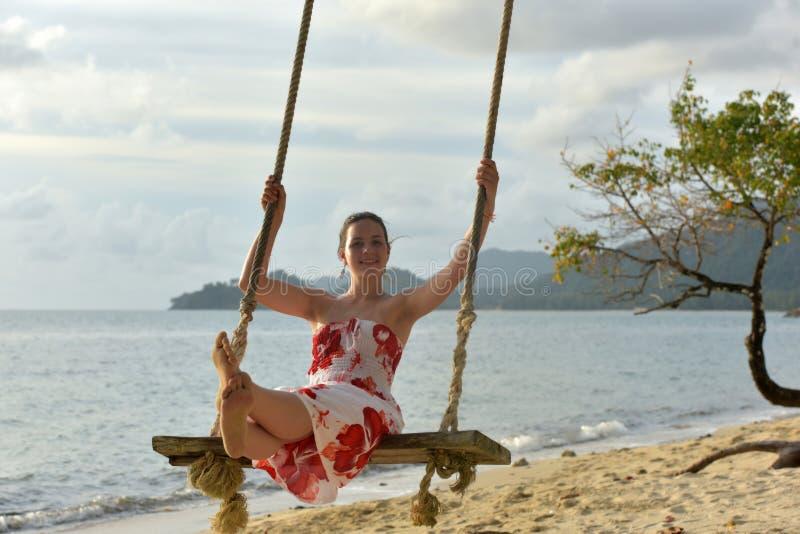 La ragazza nel bianco con i fiori rossi si veste sulla spiaggia immagini stock libere da diritti