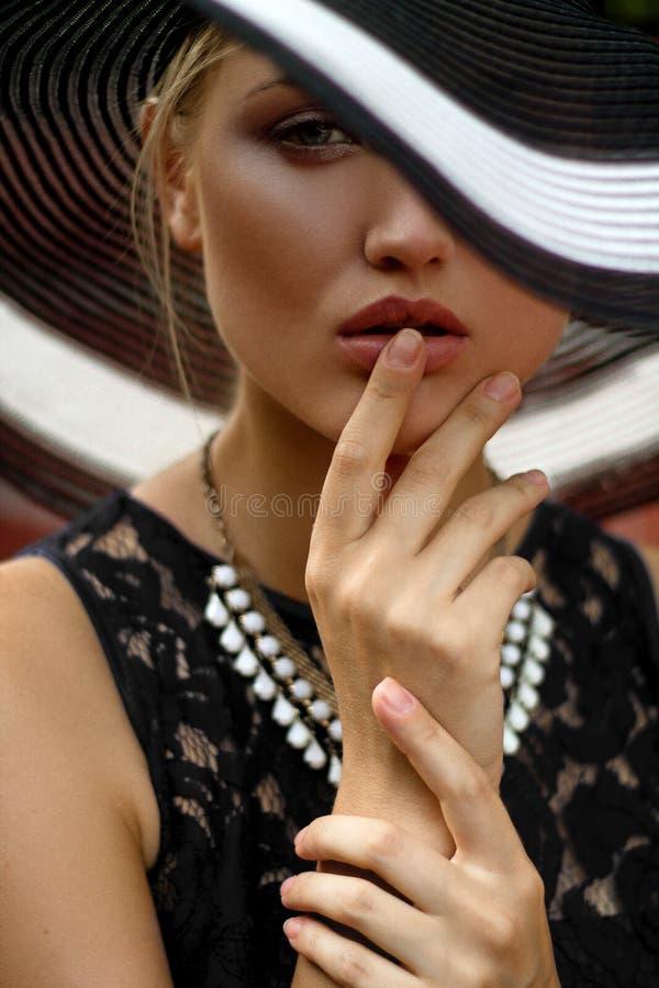 La ragazza nel cappello e nella collana fotografia stock