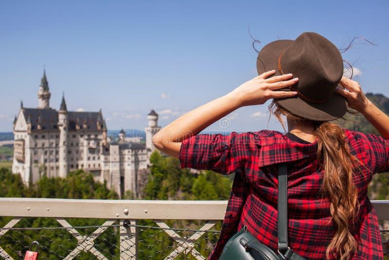 La ragazza nel castello di sguardi del cappello del Neuschwanstein in montagne alpine fotografia stock libera da diritti