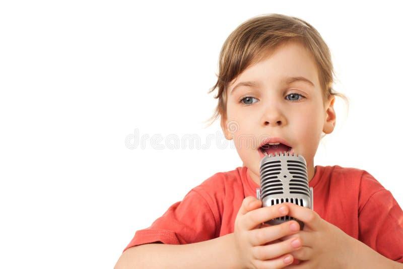 La ragazza nel colore rosso canta in microfono di vecchio stile fotografia stock