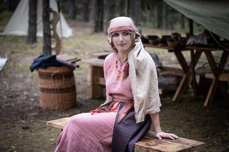 La ragazza nel costume dello slavo di Viking Age si siede su un banco di legno immagini stock