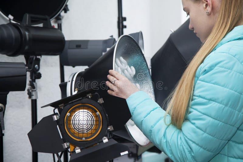 La ragazza nel deposito professionale dell'attrezzatura della foto considera la lampada della luce permanente dello studio con il fotografie stock
