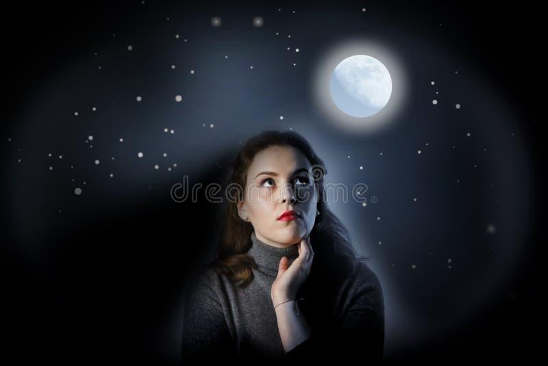 La ragazza nel grey sta guardando in pieno la luna fotografie stock libere da diritti