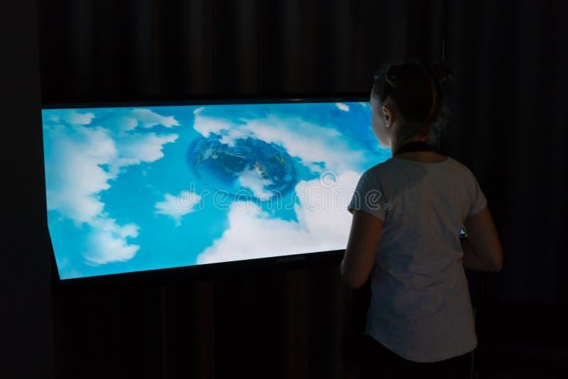 La ragazza nel museo esamina una mappa interattiva Immagine del pianeta e della città dall'aria pianeta immagine stock