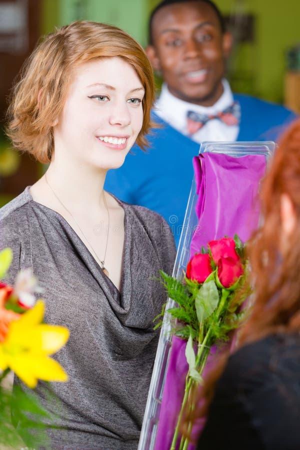 La ragazza nel negozio di fiore acquista le rose fotografia stock libera da diritti