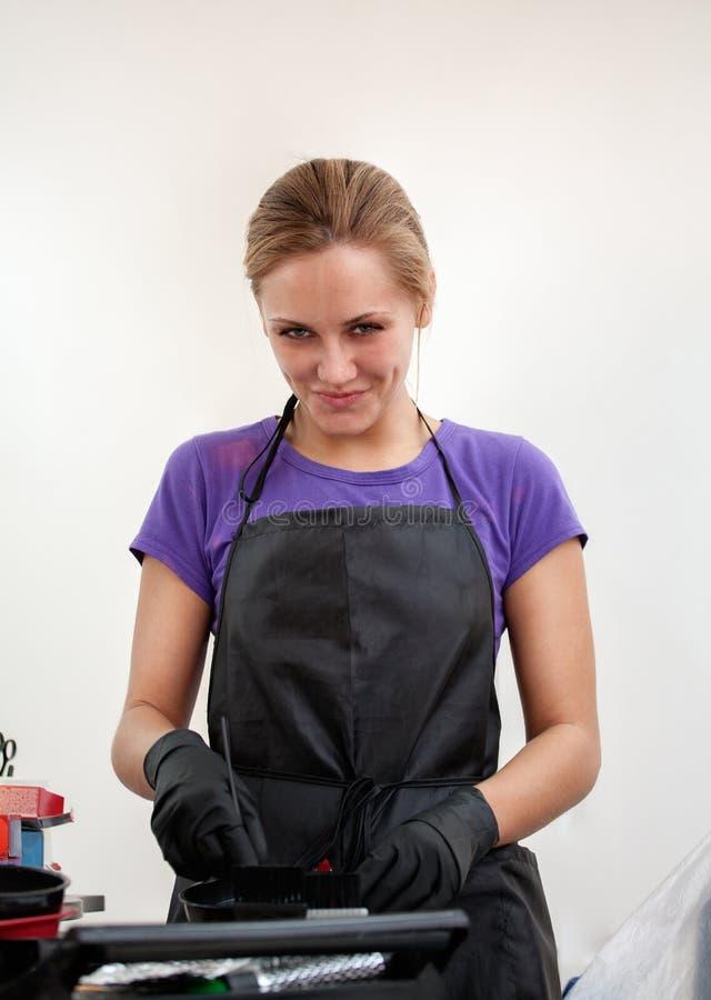 La ragazza nel parrucchiere nero dei guanti mescola la tintura per capelli fotografia stock