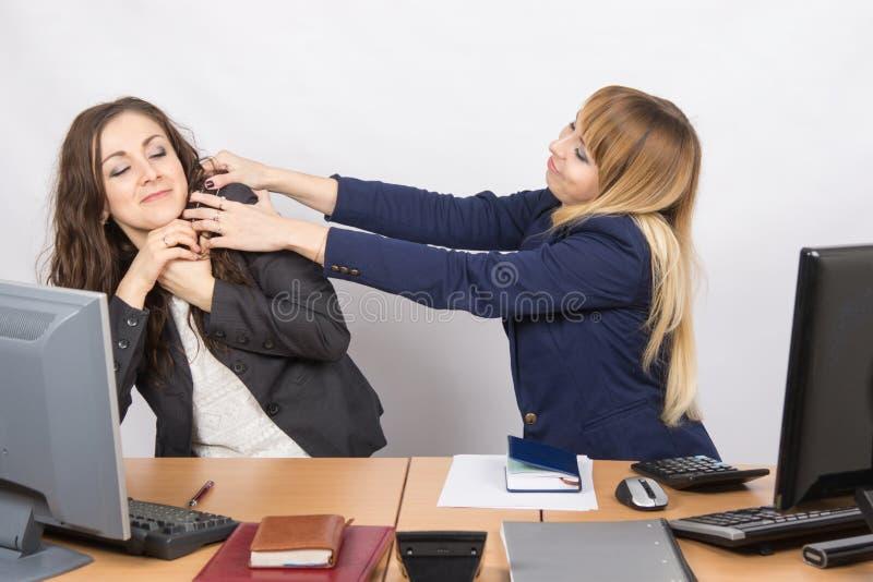 La ragazza nel posto di lavoro dell'ufficio che prova a soffocare un collega fotografia stock libera da diritti