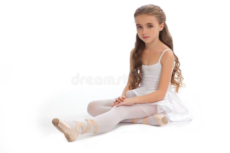La ragazza nel suo ballo copre il raggiungimento giù per toccare il suo piede fotografia stock libera da diritti