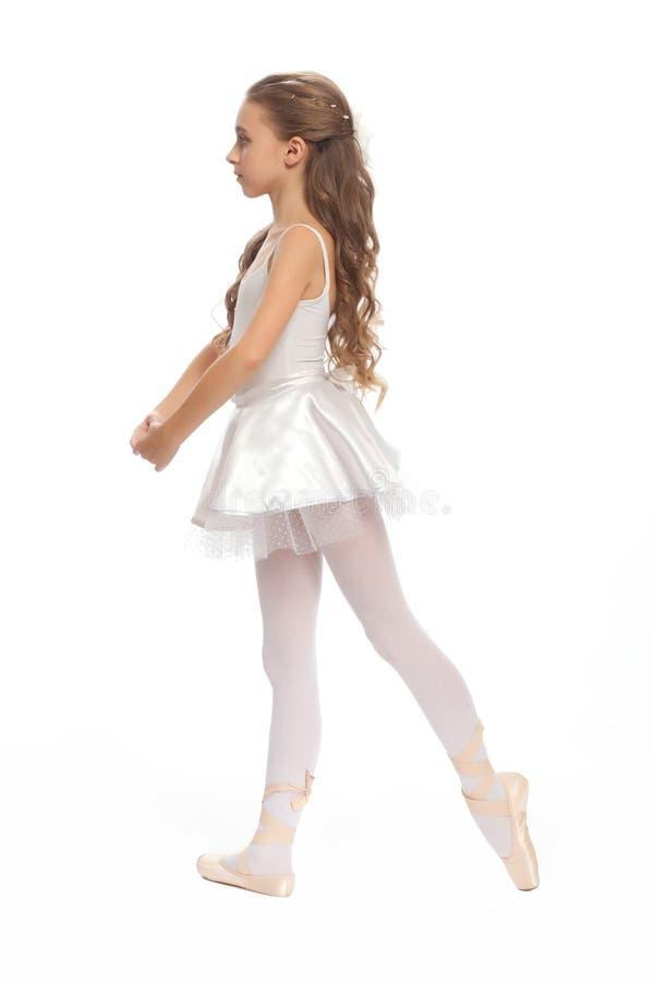 La ragazza nel suo ballo copre il raggiungimento giù per toccare il suo piede fotografia stock