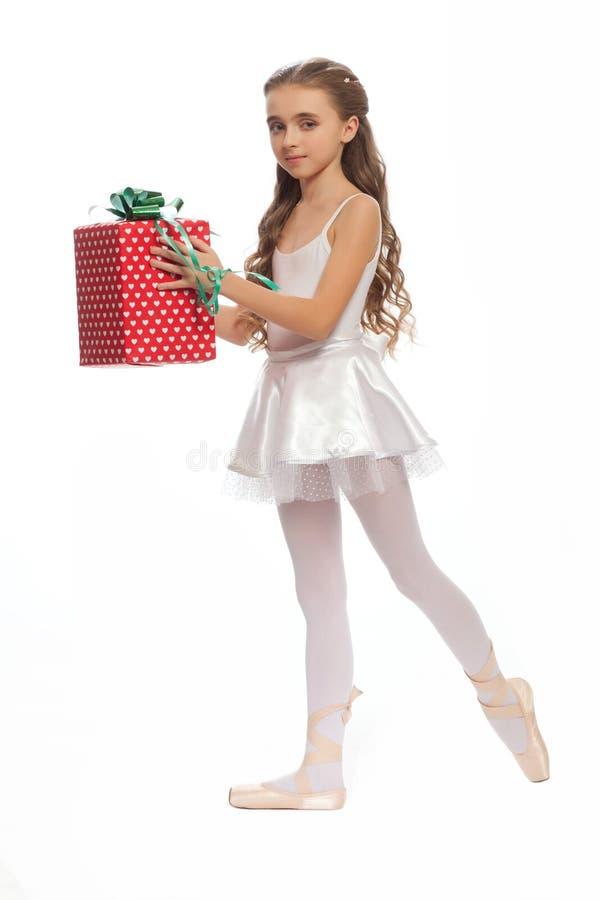 La ragazza nel suo ballo copre il raggiungimento giù per toccare il suo piede con i regali a disposizione fotografie stock