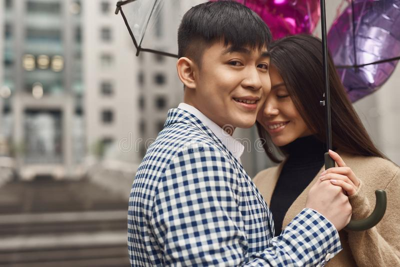 La ragazza nell'amore esamina il tipo sotto l'ombrello fotografia stock libera da diritti