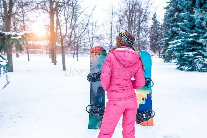 La ragazza nell'inverno su fondo di neve e degli snowboard, abete rosso verde Sta indietro in una tuta calda rosa di sport immagine stock
