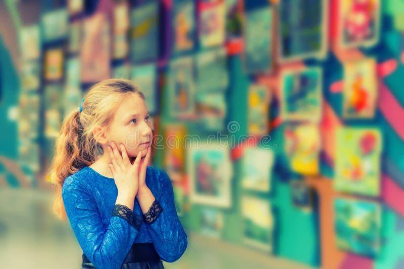 La ragazza nella galleria di arte esamina le opere d'arte ed ammira gli impianti di grandi padroni di arte fotografie stock