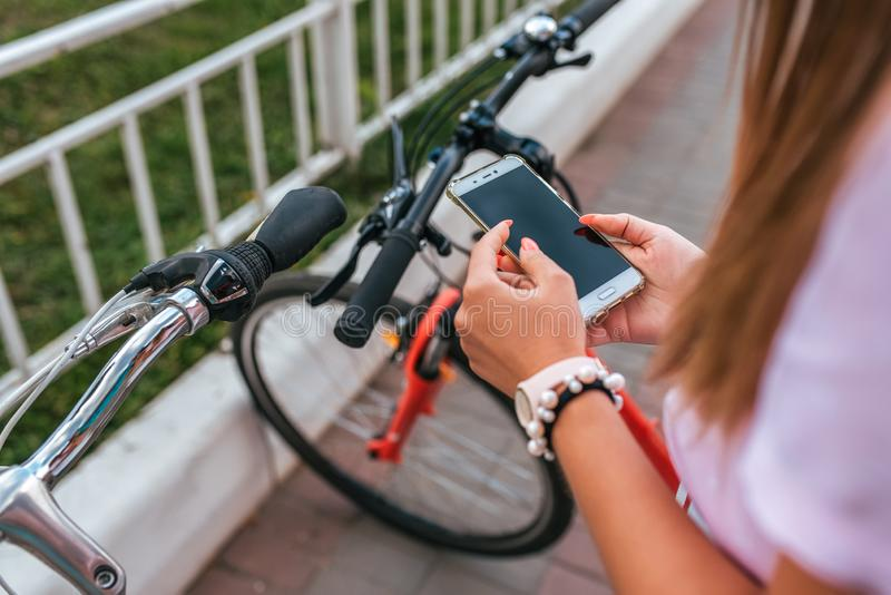 La ragazza nelle mani tiene il telefono, seleziona l'applicazione della mappa online ad Internet, ricerca di un itinerario intorn fotografia stock libera da diritti