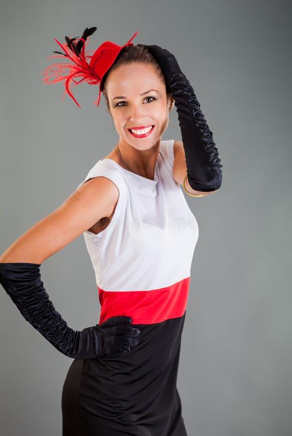 La ragazza nelle pose lunghe dei guanti del vestito bianco Nero da Red Hat sorride fotografia stock