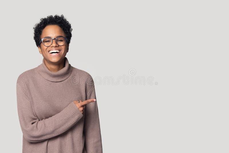 La ragazza nera sorridente in vetri indica allo spazio della copia fotografie stock