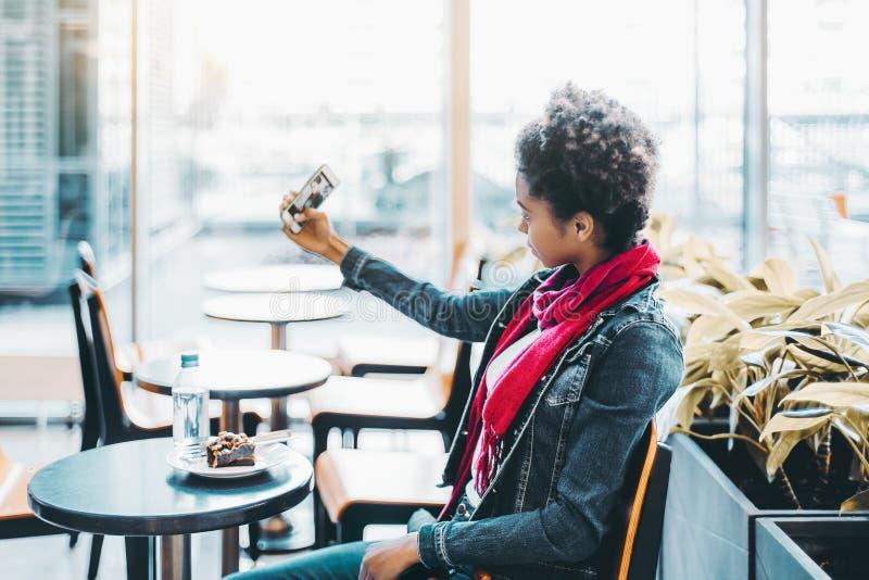 La ragazza nera sta facendo il selfie mentre si sedeva nella barra dell'ufficio fotografia stock