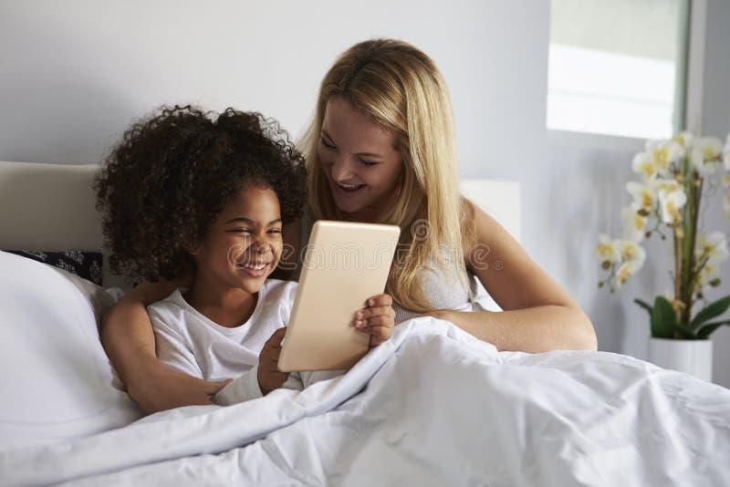 La ragazza nera tiene il computer della compressa, a letto con la mummia caucasica fotografie stock
